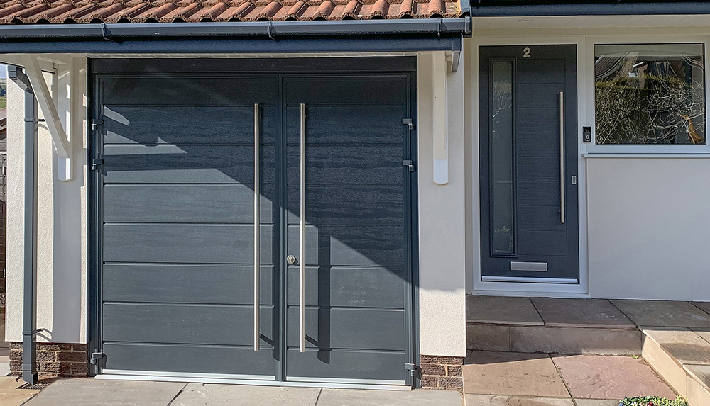 Teckentrup single centre ribbed side hinge garage door finished in anthracite grey.