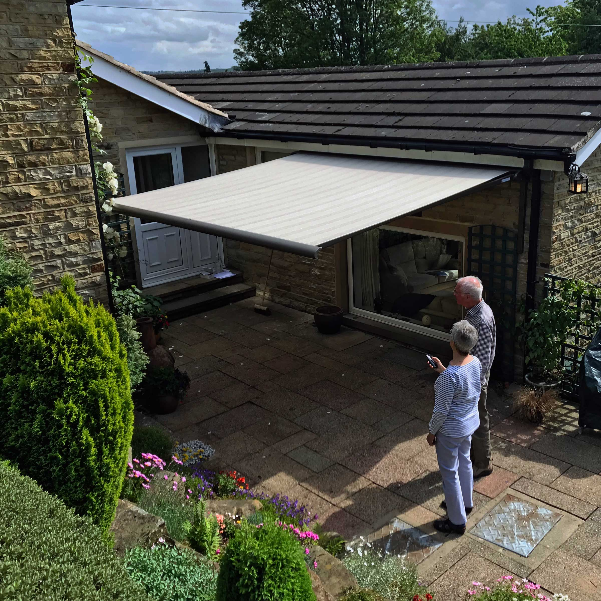 A couple operating their awning via the remote control