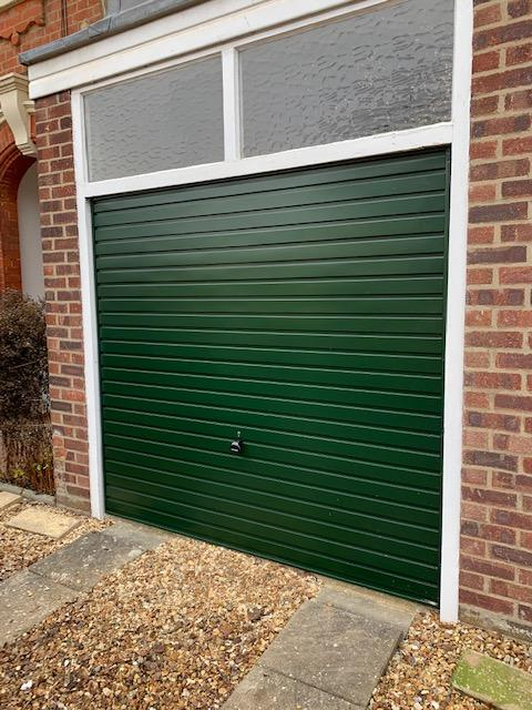 Single Garador steel horizontal canopy garage door finished in fir green.