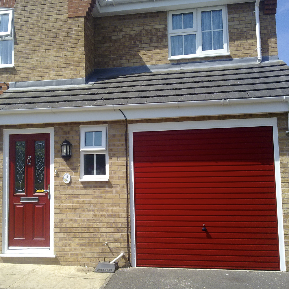 Single Garador steel horizontal canopy garage door finished in red with a white frame.
