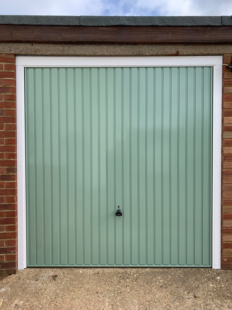 Single Garador steel vertical canopy garage door finished in chartwell green with a white frame.
