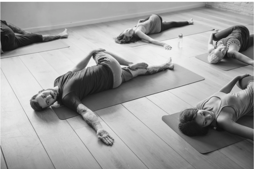 A group of people in a Pilates matwork class