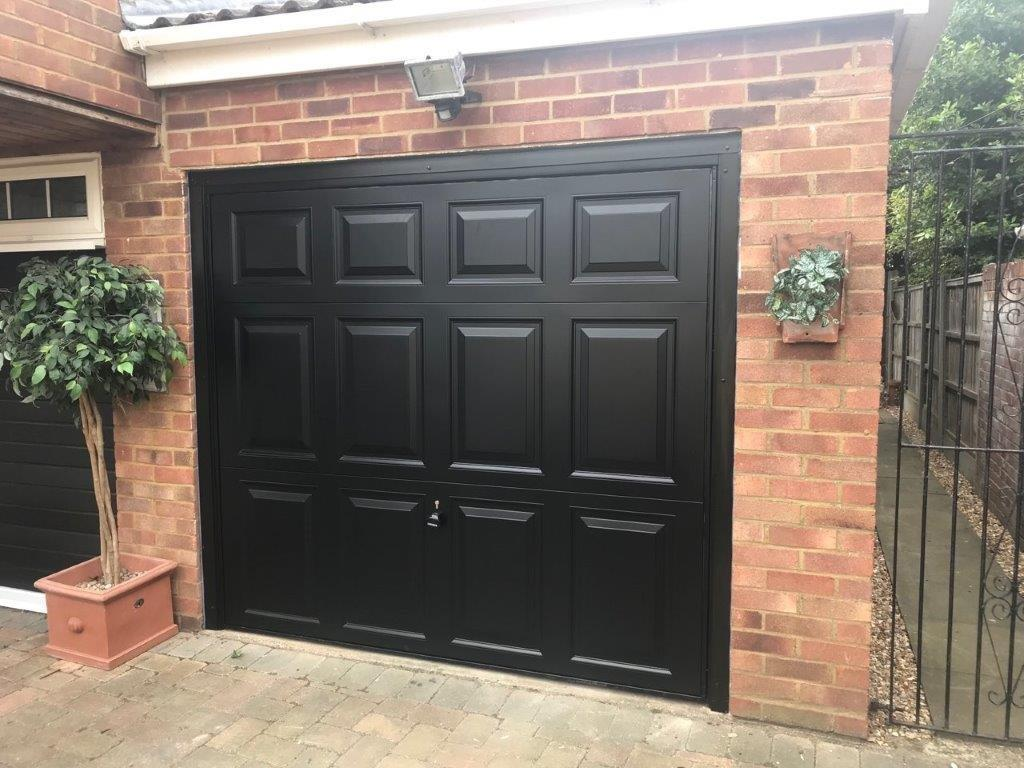 Single Garador steel georgian canopy garage door finished in black with a black frame.