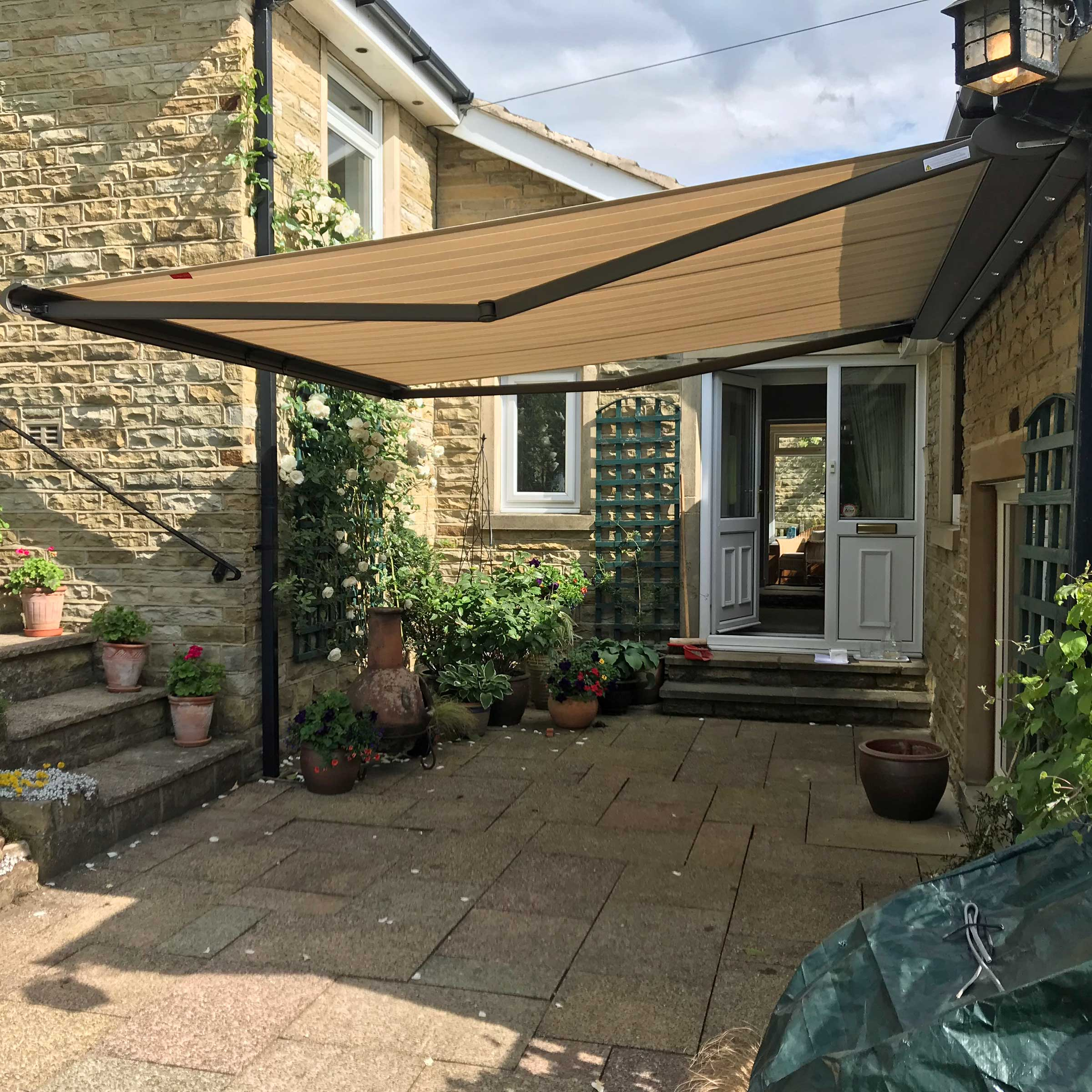 A shaded patio area covered by their Alcas awning